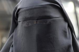 A woman who identified herself as Nayet, wearing a burqa, leaves the police station after her release in Paris