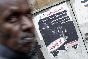 A man walks past a poster in Cairo by a group known as Youth Against Violence. The poster calls on voters not to choose Muslim Brotherhood candidates in parliamentary elections in November 2009